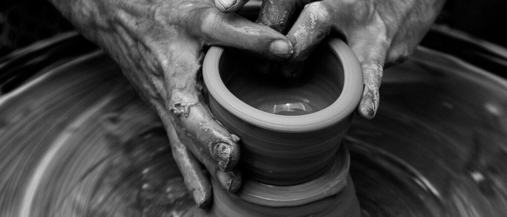 Maos fazendo jarro de barro